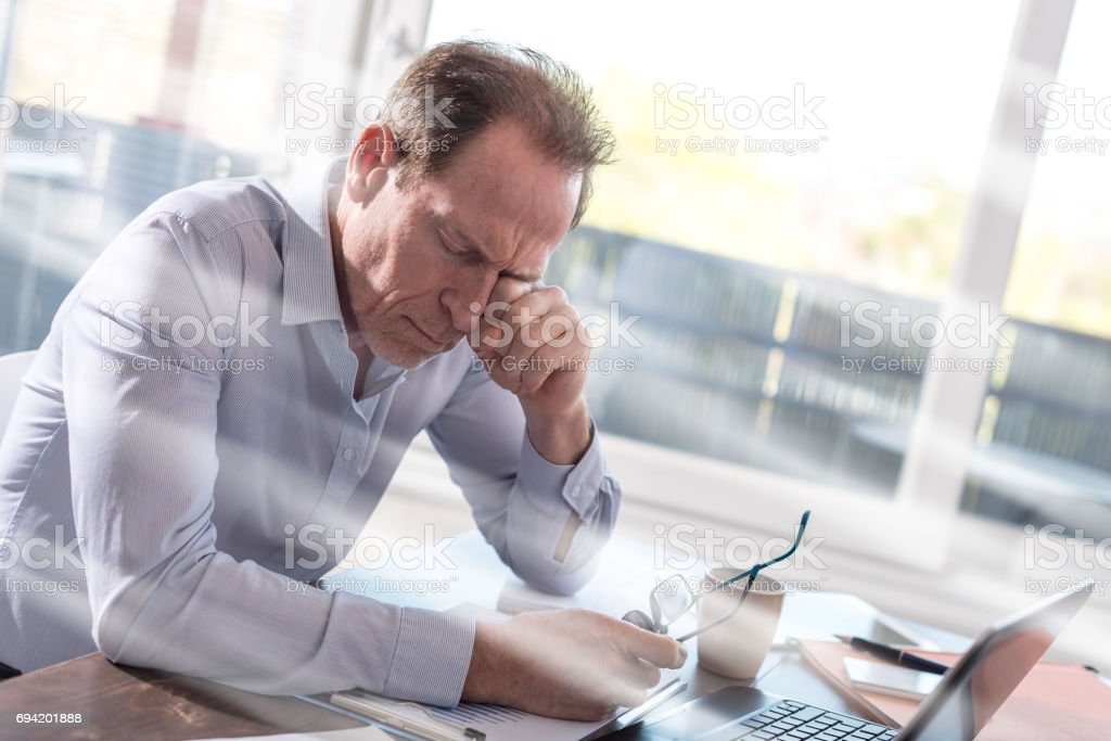 Tired businessman sitting in office, light rays effect stock photo