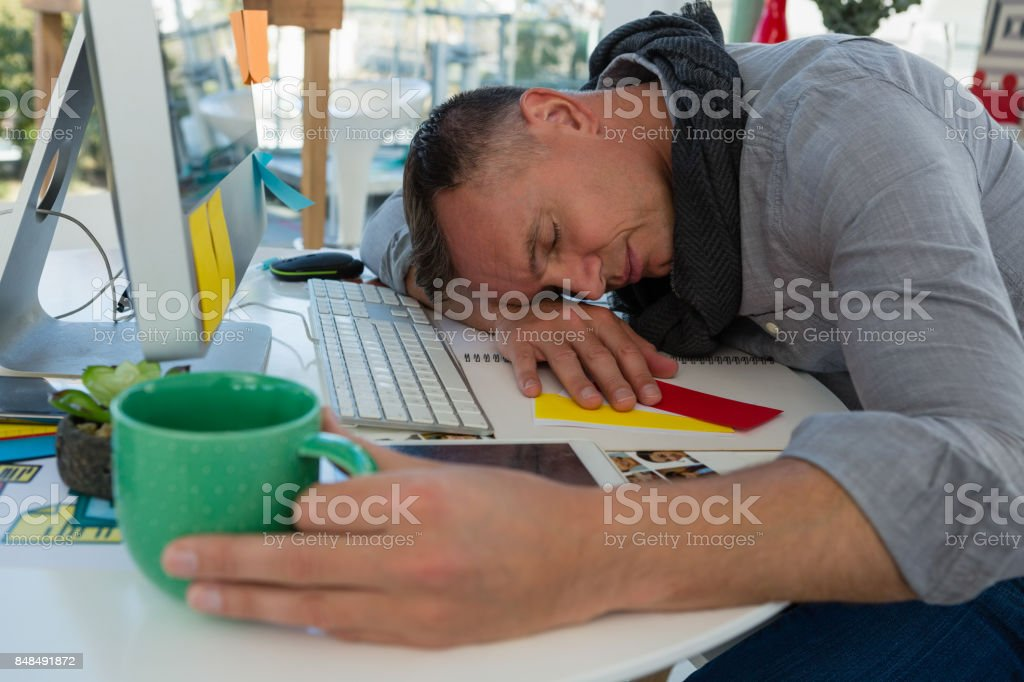 Tired businessman sleeping at desk in studio stock photo