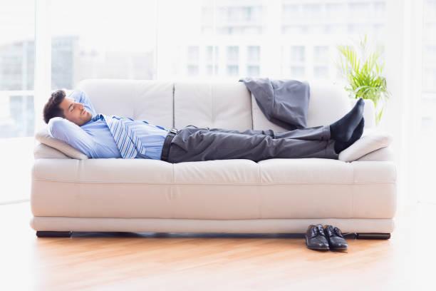 homme d'affaires fatigué, dormir sur un canapé - faire un somme photos et images de collection