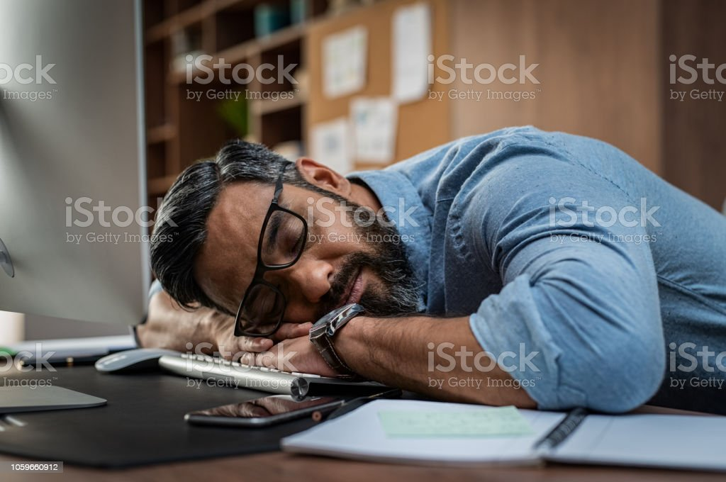 Tired businessman sleeping on computer desk stock photo