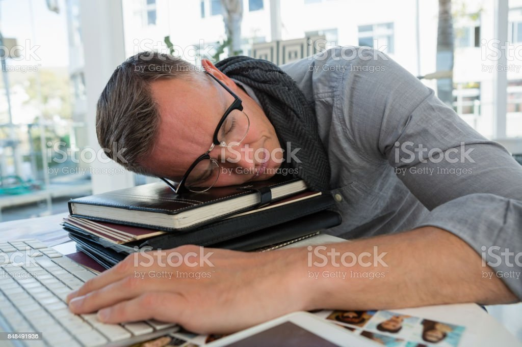 Tired businessman sleeping on files in studio stock photo