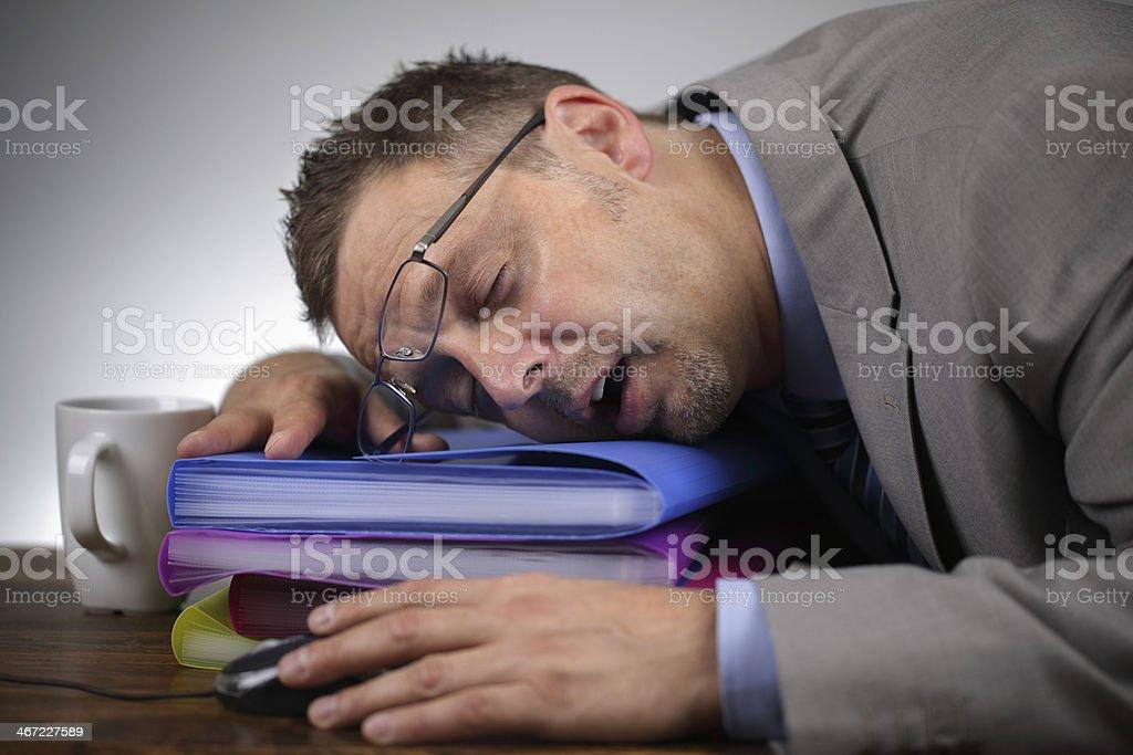 Tired businessman sleeping on files stock photo