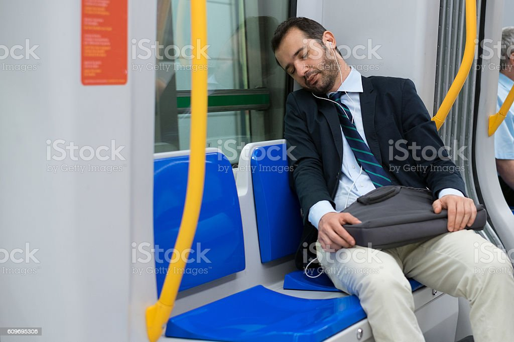 Tired businessman sleeping on the underground metro stock photo