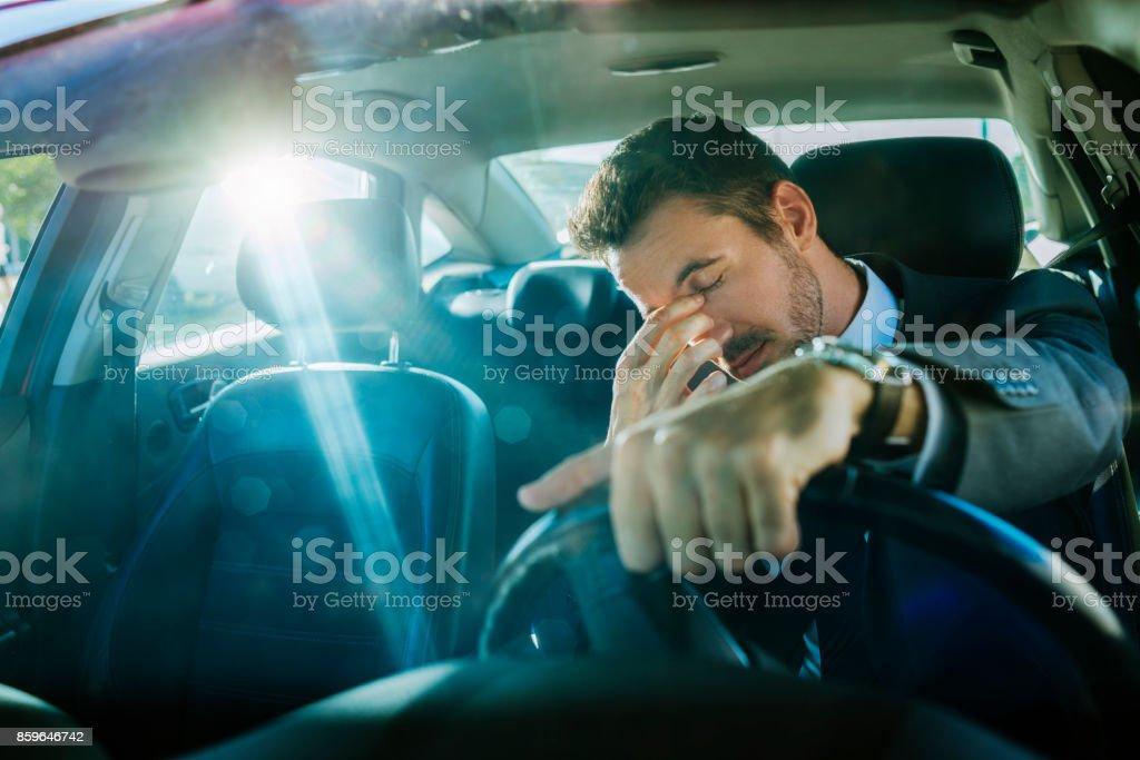 tired businessman stuck in traffic stock photo