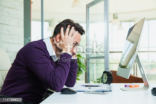 istock Tired businessman student hold his head. 1147399022