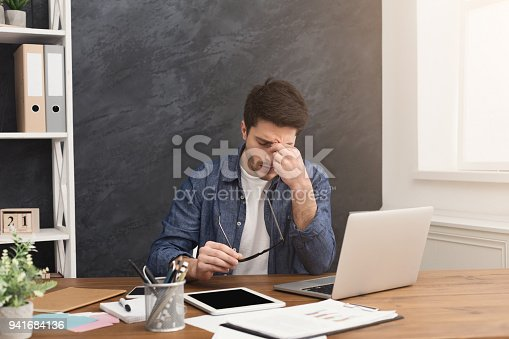 626964348istockphoto Tired businessman with laptop in modern white 941684136