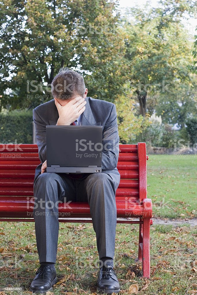 Tired businessman with laptop stock photo