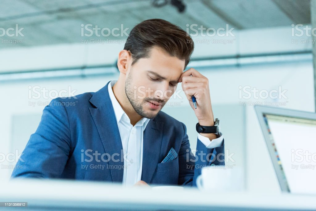 Tired businessman working at creative office Tired businessman sitting at desk in creative office. Handsome male professional is at workplace. He is in suit. 30-39 Years Stock Photo