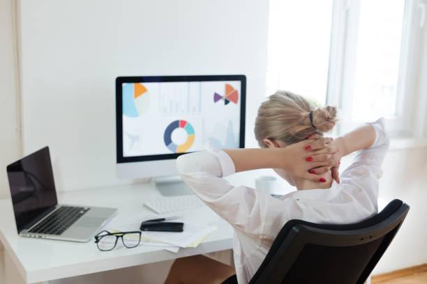 müde geschäftsfrau im büro - rückenschmerzen beim sitzen stock-fotos und bilder