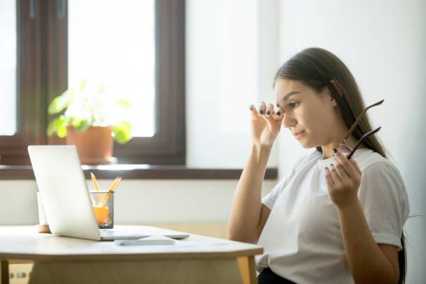 Femme d'affaires fatigué tenant des lunettes et se frottant les yeux dans le Bureau à domicile - Photo