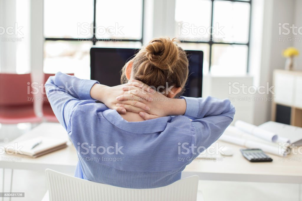 Tired businesswoman holding her nape stock photo