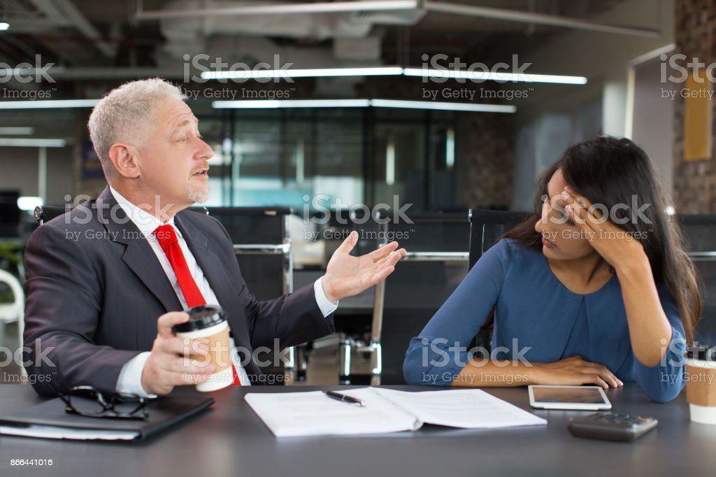 Tired businesswoman listening to senior colleague stock photo