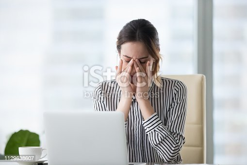 1049512672 istock photo Tired businesswoman massaging eyes feeling strain fatigue headache relieving pain 1129638607