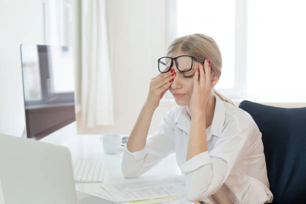 tired businesswoman rubbing eyes in office - stress women stock photos and pictures