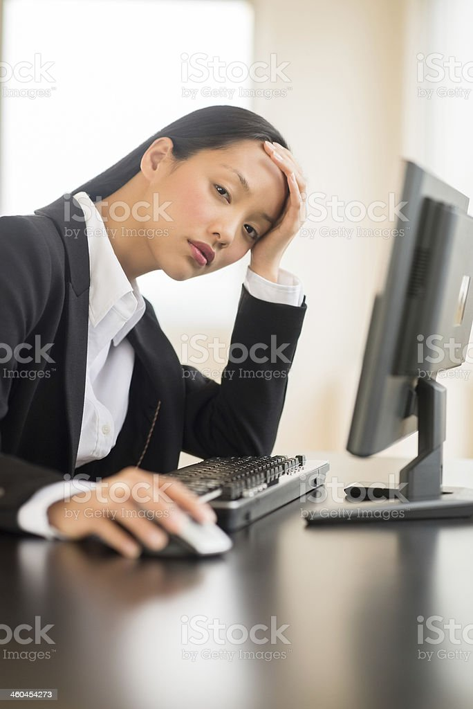 Tired Businesswoman Using Computer At Desk royalty-free stock photo