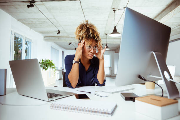 Tired businesswoman with head in hands at desk stock photo
