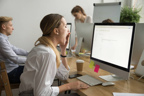 tired businesswoman yawning working on computer sitting at office desk - sleeping in work stock photos and pictures