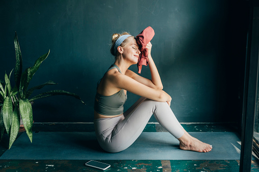 Smiling woman wiping off sweat with a towel after a home workout.