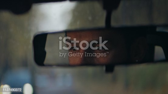 Rear mirror view. Sleepy, tired, fatigued, exhausted young man closing eyes