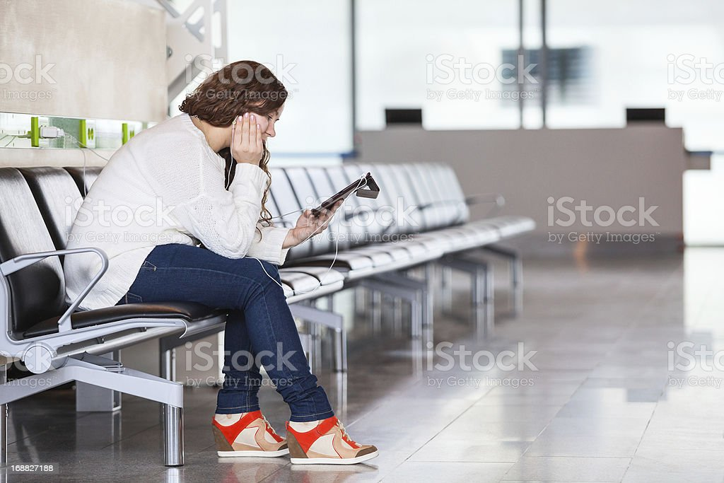 Tired Caucasian woman with devices sitting in airport lounge royalty-free stock photo