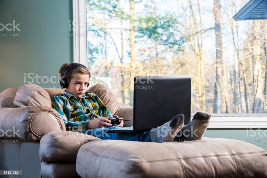 A tired child playing video games on a laptop stock photo