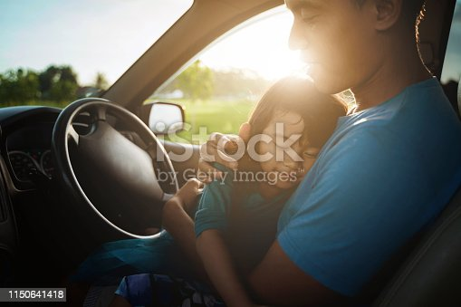 972962180 istock photo tired child sleeping on father's lap in the car 1150641418