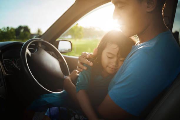 enfant fatigué dormant sur les genoux du père dans la voiture - child car sleep photos et images de collection