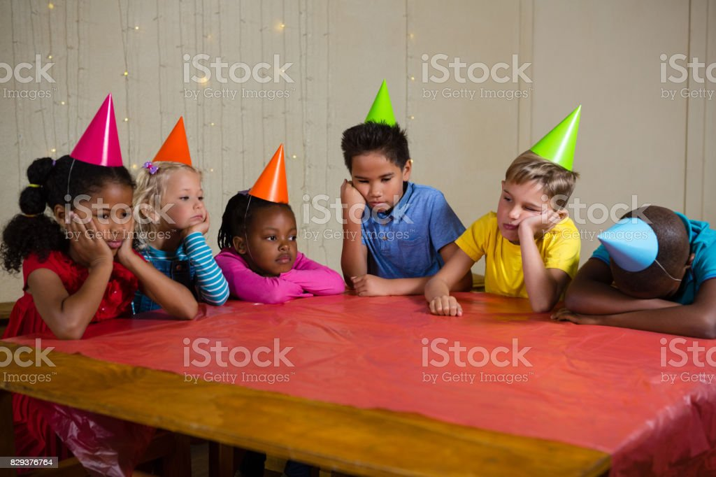 Tired children sitting at table stock photo