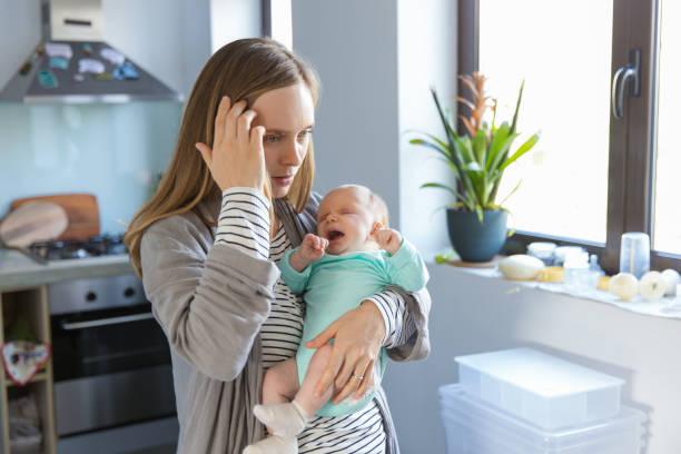 Müde besorgt neue Mutter schaukeln weinende Baby – Foto