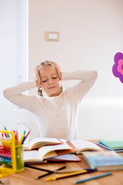 müde niedliche blonde schulmädchen in stress arbeiten hausaufgaben - kreatives schreiben übungen stock-fotos und bilder