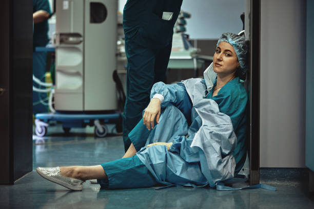 Tired doctor sitting after surgery in the hospital corridor. Great burden on doctors and medicine. Rest after work. Epidemic, lack of medical personnel, medical wards stock photo