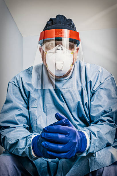 Tired doctor/nurse wearing PPE sitting looking at the camera with hands clasped