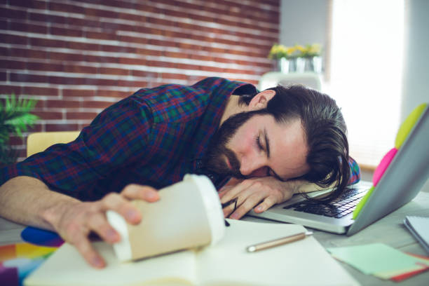 tired editor holding disposable cup - sleeping in work stock photos and pictures