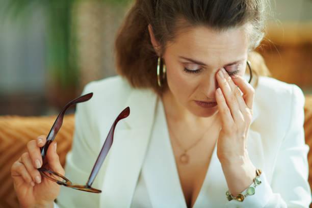 tired elegant housewife glasses rubbing eyes