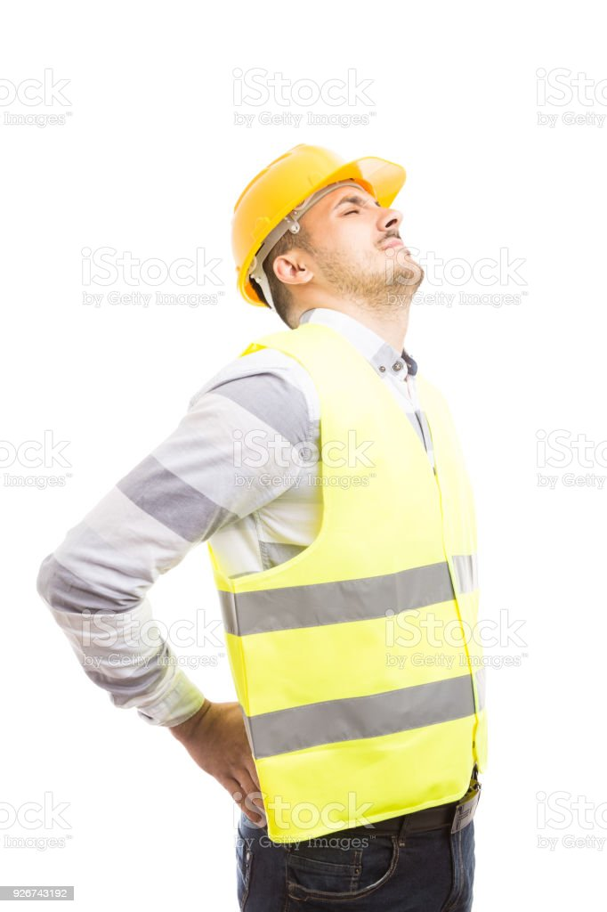 Tired engineer or builder suffering lower back lumbar pain stock photo