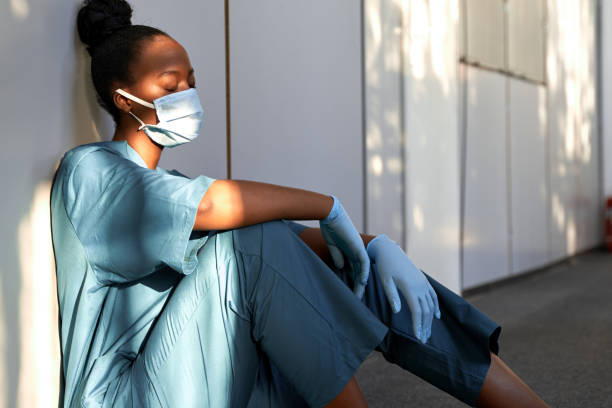 Tired exhausted female african scrub nurse wears face mask blue uniform gloves sits on hospital floor. Depressed sad black ethic doctor feels fatigue burnout stress, lack of sleep, napping at work. Tired exhausted female african scrub nurse wears face mask blue uniform gloves sits on hospital floor. Depressed sad black ethic doctor feels fatigue burnout stress, lack of sleep, napping at work. stressed woman wearing mask stock pictures, royalty-free photos & images
