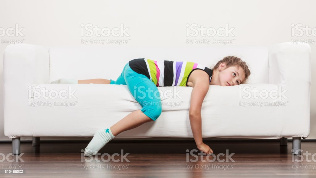 Tired exhausted lazy little girl kid lying on sofa stock photo