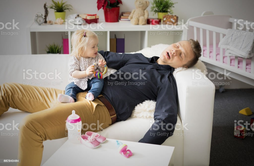 Tired father sleeping with baby on his lap. stock photo