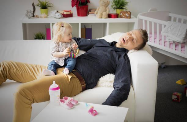 cansado pai dormindo com o bebê no colo dele. - novo bebê - fotografias e filmes do acervo