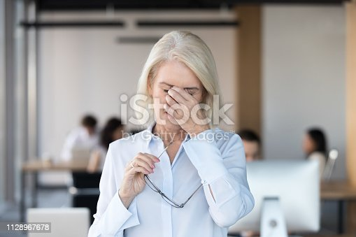 1049512672 istock photo Tired fatigued senior female employee taking off glasses feeling eyestrain 1128967678