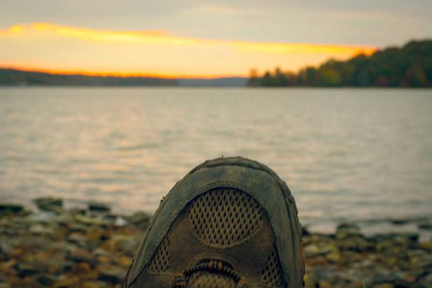 Tired feet rest on the shore of a lake after a hike stock photo