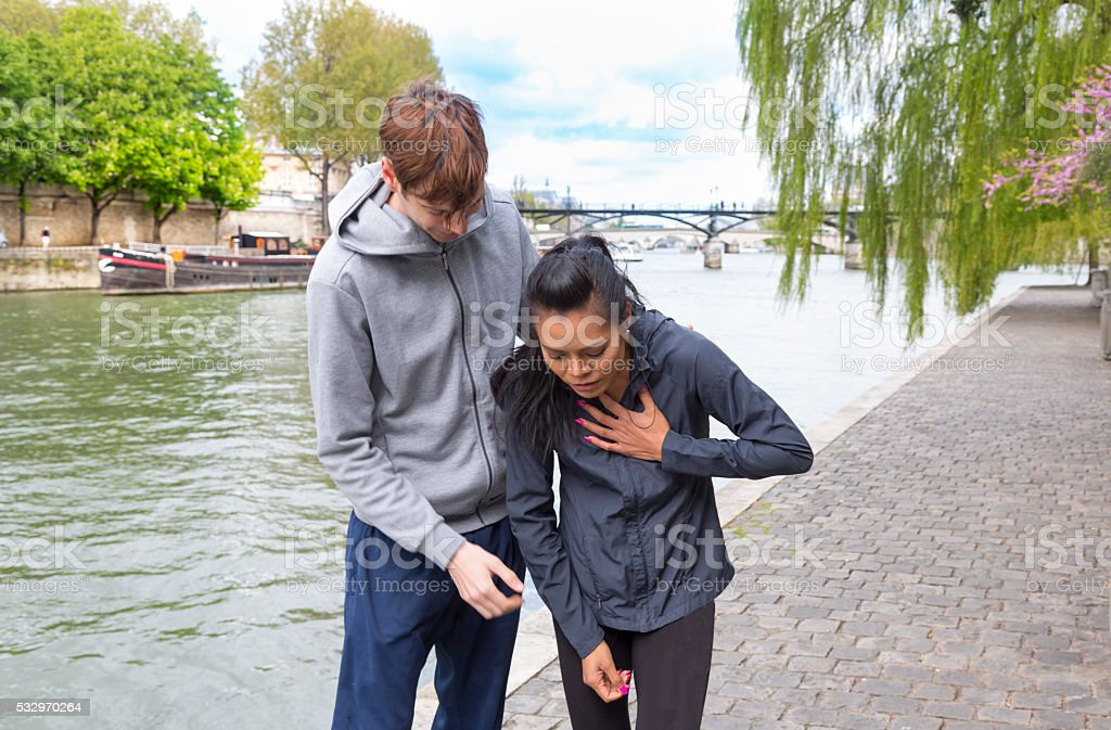 Tired female jogger helped by male friend, Paris, France. stock photo