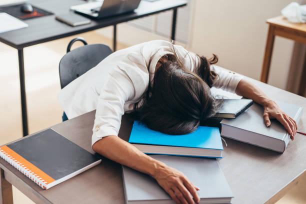 Müde, schlafen auf Schreibtisch Gesicht und Hände Studentin auf Bücher – Foto