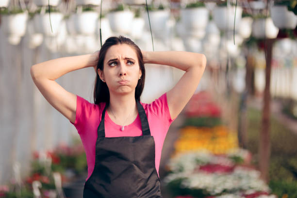 Tired Female Worker in Floral Greenhouse  Feeling Overwhelmed Stressed business owner having a bad season in agricultural field of work quitting a job stock pictures, royalty-free photos & images
