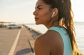 Tired fitness woman sweating taking a break listening to music on phone after difficult training. Young woman listening to music with earphones on smart phone app for fitness motivation