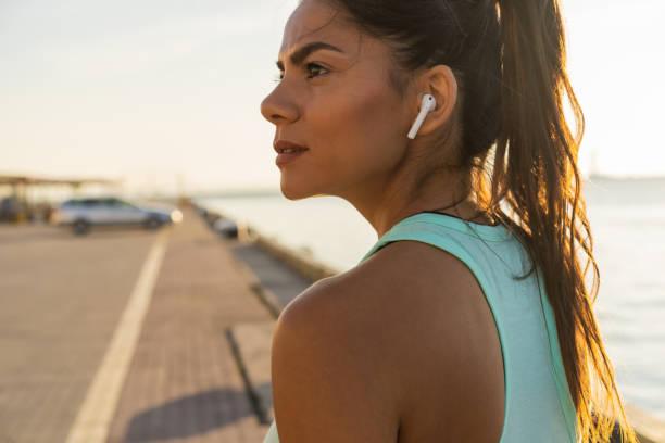 femme fitness fatigués transpiration prend une pause en écoutant de la musique sur le téléphone après une formation difficile. - écouteurs intra auriculaires photos et images de collection