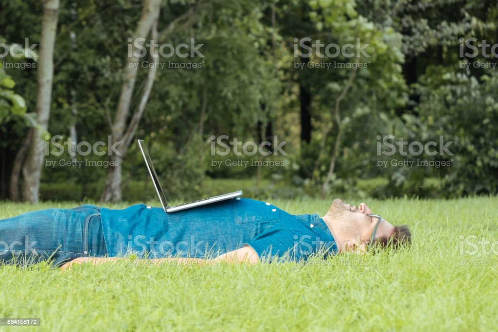Tired freelancer lying in the park with laptop computer and resting royalty-free stock photo