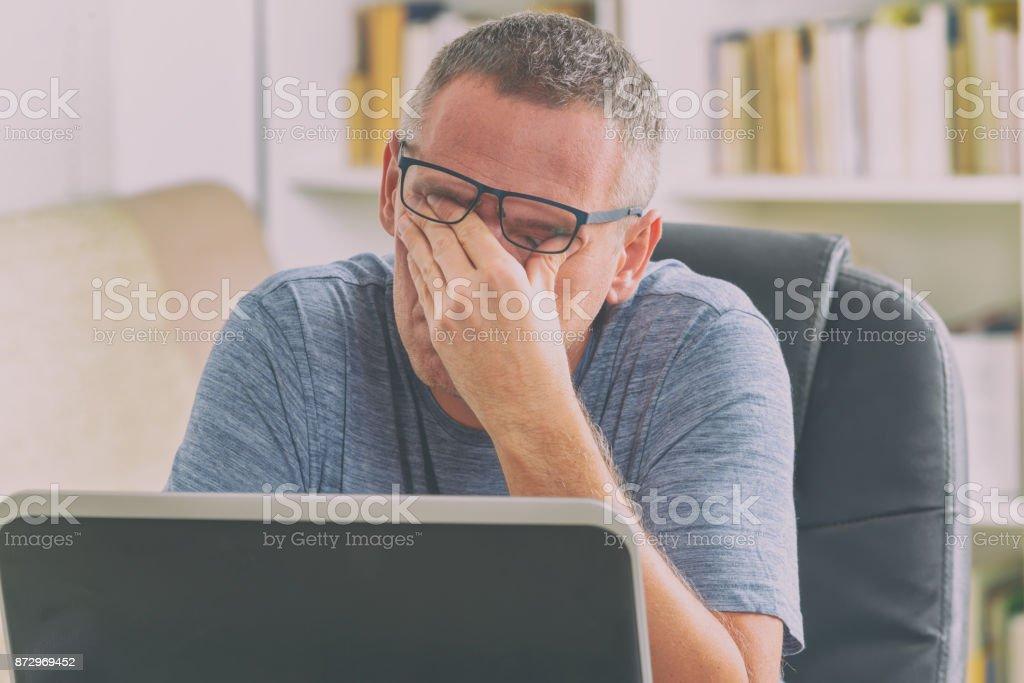 Tired freelancer man rubbing his eyes royalty-free stock photo