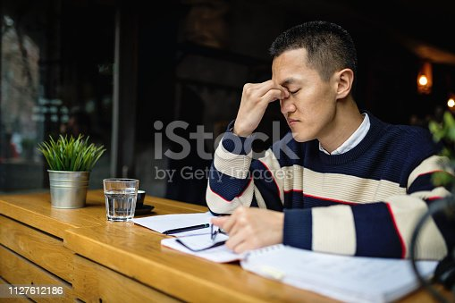Succesful young japanese freelance worker organizing his time while sitting in a cafe