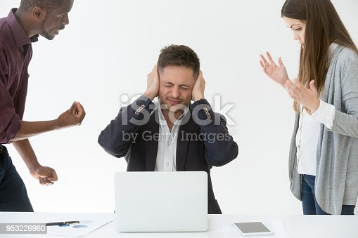 istock Tired from work or noise businessman closing ears with hands 953226960